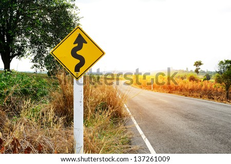 Winding road sign in the forest and mountain