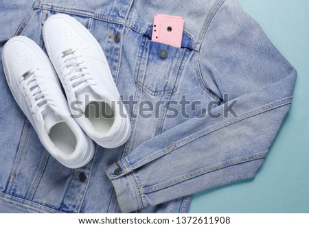 Flat lay style white hipster sneakers with a denim jacket, audio cassette on pastel blue background. Retro pop culture, top view #1372611908