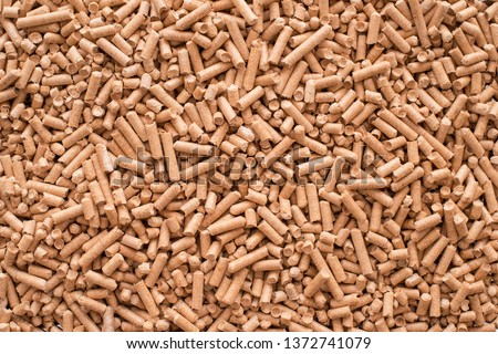 Wooden pellets background, pattern. Close up natural wood pellet. Ecological heating, renewable energy Biofuels. Top view. Flat lay ecological fuel for solid fuel boilers.  #1372741079