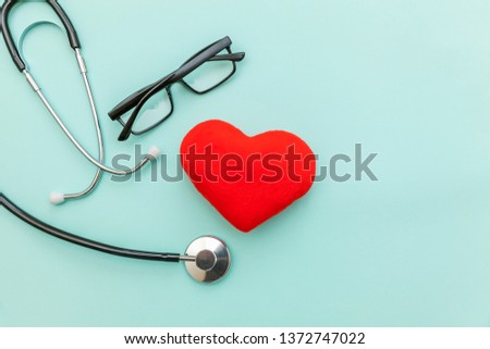 Simply minimal design medicine equipment stethoscope or phonendoscope glasses and red heart isolated on trendy pastel blue background. Instrument device for doctor. Health care life insurance concept #1372747022