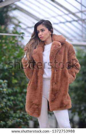 posing girl with brown fur in front of the mansion and greenhouse #1372753988