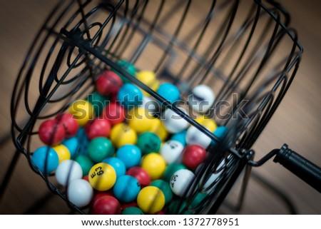 Multi-colored bingo balls in cage sitting on a desk. #1372778951