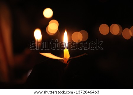 Hand holding a candle at night with bokeh on a dark background #1372846463