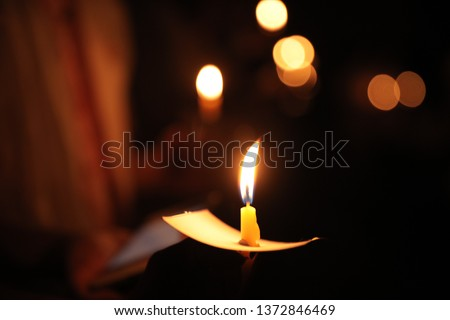Hand holding a candle at night with bokeh on a dark background #1372846469