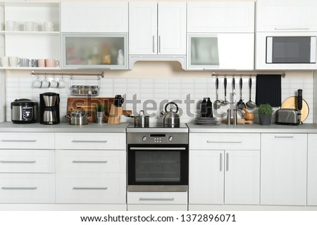 Different appliances, clean dishes and utensils on kitchen counter #1372896071