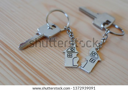 Pendant of key ring in shape of house divided in two parts on wooden background, closeup view. Dividing house when divorce, division of property and real estate.  #1372939091