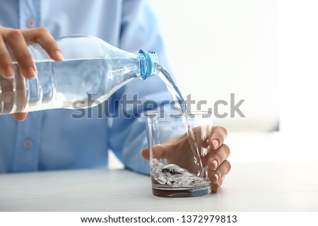 Woman pouring water into glass on table #1372979813