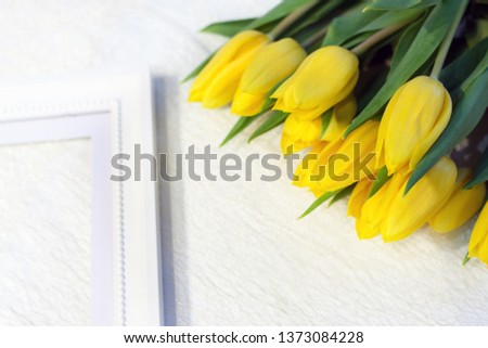 The white photo frame with yellow tulips. Free space for text #1373084228