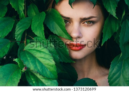 Bright makeup beautiful female face and green leaves of shrubs                         #1373120699
