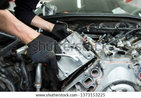 The auto mechanic deconstructs the internal combustion engine #1373153225