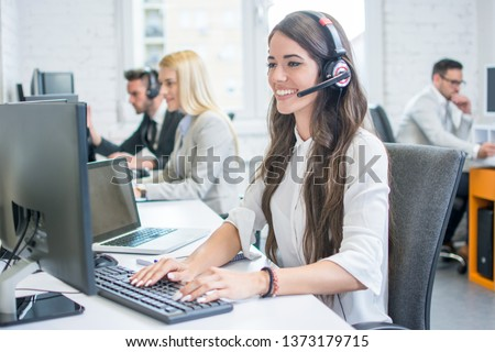 Beautiful young woman with headset working on computer while talking with client in call center. Online customer support. #1373179715