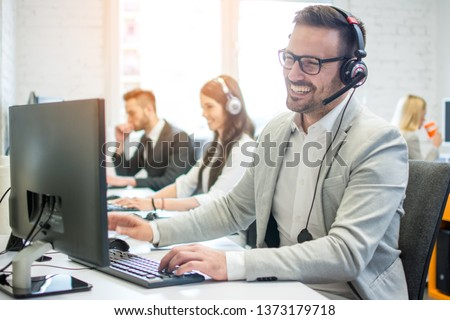 Cheerful friendly online technical operator agent with headphones and microphone talking with client in customer support office #1373179718