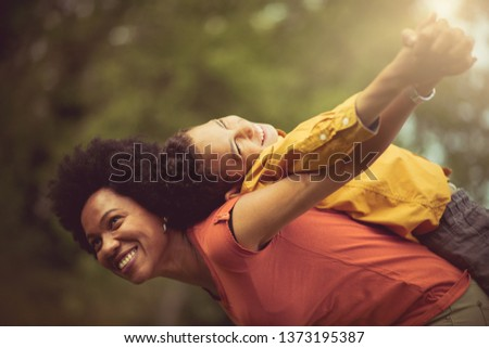 He's flying with his mom. Mother and son in the park. #1373195387