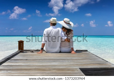 Elegant honeymoon traveler couple hugging on a wooden jetty and enjoy their tropical holiday in the Maldives islands #1373203964