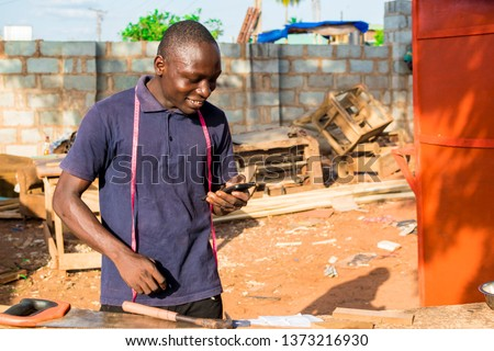 african carpenter smiling while checking his phone in his workshop #1373216930