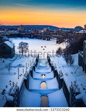 OTTAWA, CANADA - Rideau Canal Locks with beautiful winter sunset and birds flying by. Blue, yellow and orange sky with lots of snow on canal waterway. Canadian winter scene. Ottawa, Ontario, Canada #1373313260