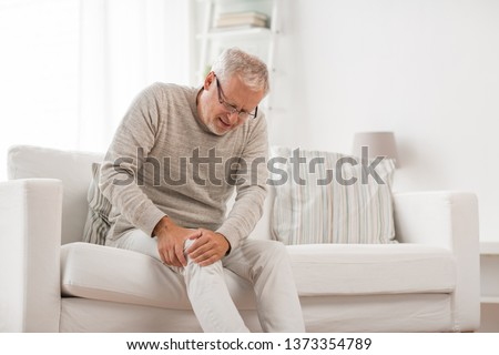 people, health care and problem concept - unhappy senior man suffering from knee ache at home #1373354789