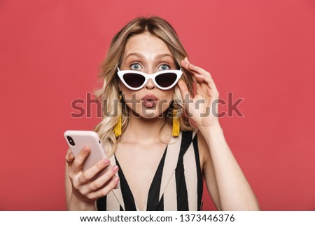 Photo of a beautiful shocked amazing young woman posing isolated over red coral background using mobile phone. #1373446376