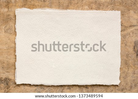 small sheet of blank white Khadi rag paper from South India against brown amate bark paper #1373489594