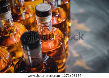 Small liquor production based on maple syrup. Multitude of pure alcohol bottles  not labeled. Bottles placed in a row. #1373608139