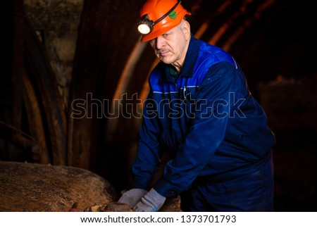 elderly man in a protective suit and helmet. Miner in mine #1373701793