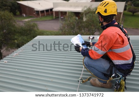 Rope access inspector technician holding looking at the paper work while inspecting fall arrest, fall restraint roof anchor point horizontal safety line Sydney, CBD, Australia    Royalty-Free Stock Photo #1373741972