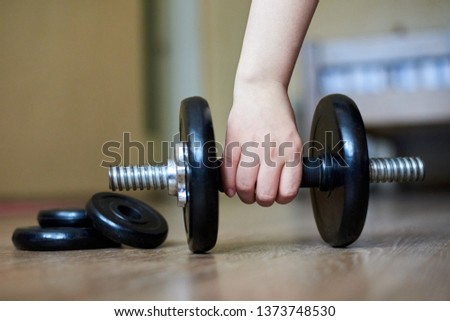 The hand of the girl takes a dumbbell from the floor at home, home sports, healthy lifestyle, close-up #1373748530