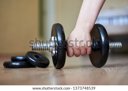 The hand of the girl takes a dumbbell from the floor at home, home sports, healthy lifestyle, close-up #1373748539
