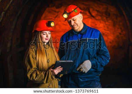A beautiful young girl in a red helmet and with a electronic tablet in her hands is standing with a miner in a coal mine. Business plan discussion. #1373769611