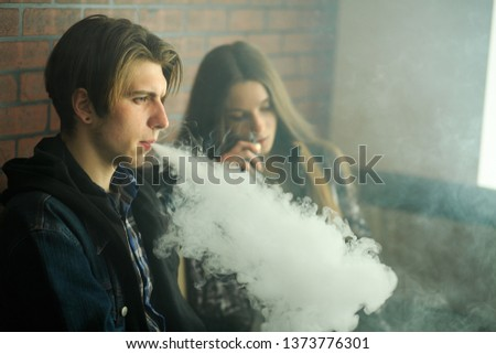 Vape teenagers. Young cute girl in sunglasses and young handsome guy smoke an electronic cigarettes in the vape bar. Bad habit that is harmful to health. Vaping activity. #1373776301