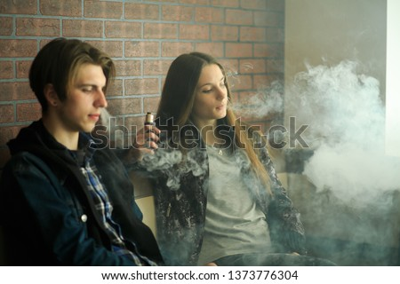 Vape teenagers. Young cute girl in sunglasses and young handsome guy smoke an electronic cigarettes in the vape bar. Bad habit that is harmful to health. Vaping activity. #1373776304