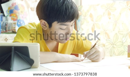Asian mother helping her son doing homework on white table. #1373797838