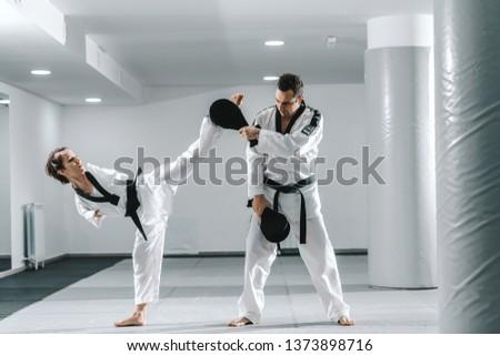 Caucasian handicapped highly motivated girl practicing taekwondo with her training. Girl kicking kick target. #1373898716