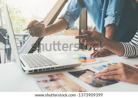 Asian advertising designer creative start-up team discussing ideas in office. #1373909399