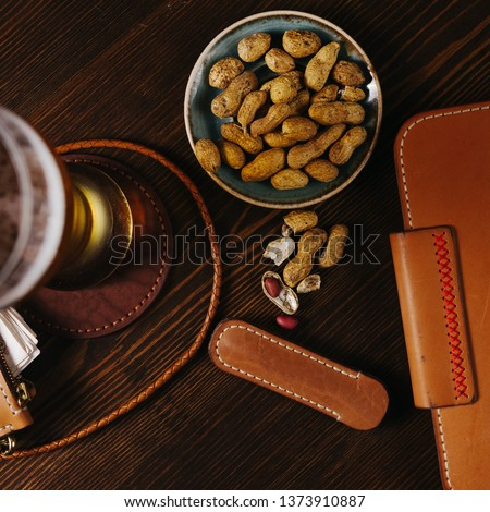 Leather notebook in the bar with beer and nuts on a wooden table, Flat Lay #1373910887