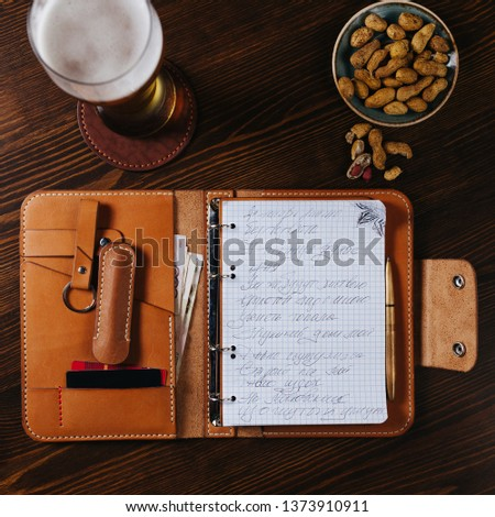 Leather notebook in the bar with beer and nuts on a wooden table, Flat Lay #1373910911