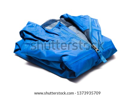 Folded blue zipper windbreaker jacket, rain proof and waterproof hiking Gore-Tex jacket hoodie. Track jacket sport nylon full zip isolated on white. Folded clothes. Outer layer garment for travel. #1373935709