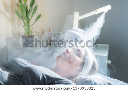 Beauty treatment of face with ozone facial steamer in beauty center. Beaultiful Blonde Girl. Royalty-Free Stock Photo #1373953823