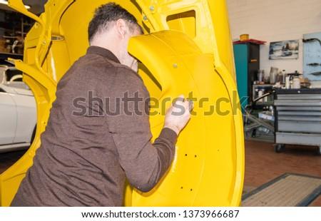 Car mechanic screws car parts together again after restoration - Serie Repair Workshop #1373966687