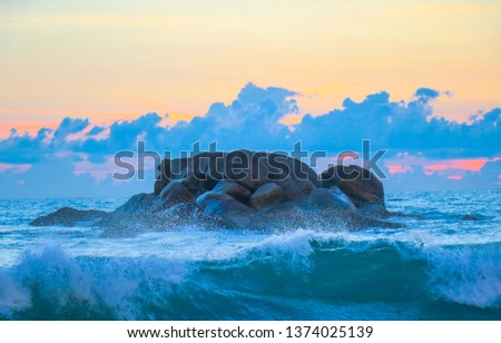Rock in the sea waves at sunset beautiful, sea wave impact the stone on beach in the sunset time #1374025139