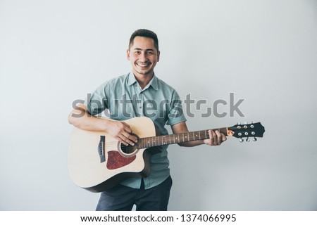 Cheerful guitarist. Cheerful handsome young man playing guitar and smiling while standing on white wall background #1374066995