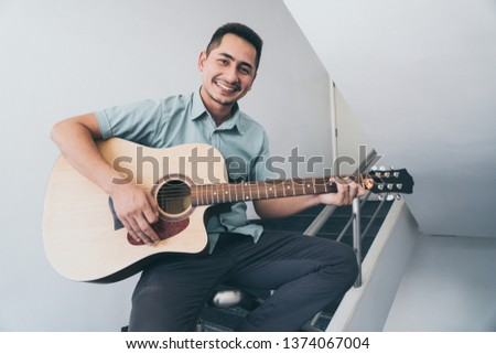 Cheerful guitarist. Cheerful handsome young man playing guitar and smiling while standing on white wall background #1374067004
