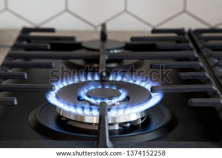 Gas burner on black modern kitchen stove. kitchen gas cooker with burning fire propane gas #1374152258