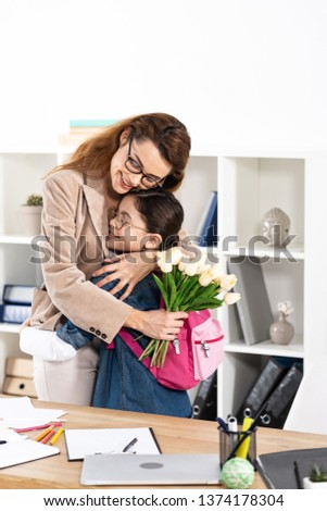 happy mother hugging cute daughter and holding flowers in office  #1374178304