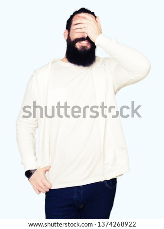 Young man with long hair and beard wearing sporty sweatshirt smiling and laughing with hand on face covering eyes for surprise. Blind concept. #1374268922