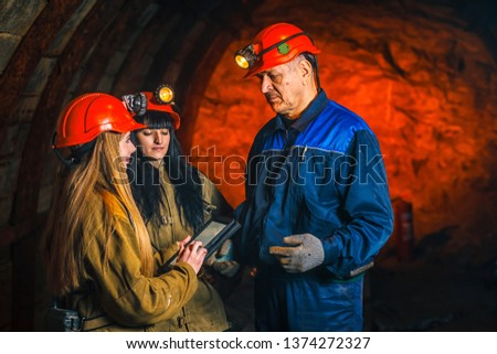 A beautiful young girl in a red helmet and with a electronic tablet in her hands is standing with a miner in a coal mine. Business plan discussion. #1374272327