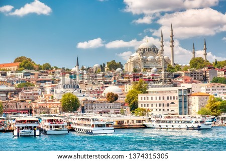 Touristic sightseeing ships in Golden Horn bay of Istanbul and view on Suleymaniye mosque with Sultanahmet district against blue sky and clouds. Istanbul, Turkey during sunny summer day. #1374315305