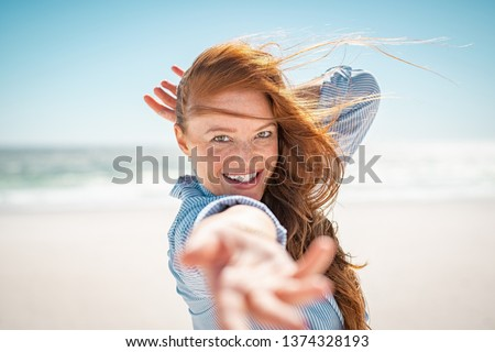 Cheerful young woman with red hair enjoying holiday at beach. Beautiful mature woman at sea during a windy day. Attractive girl smiling and looking at camera while feeling free at beach. #1374328193