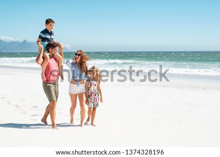 Smiling parents with children at sea. Cute son sitting on father shoulder with mother and sister walking while talking. Happy family with two children enjoying summer holiday at beach with copy space. #1374328196
