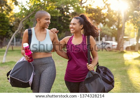 Cheerful smiling friends in sportswear holding gym bag and bottle in park. Multiethnic women going to park for fitness workout. Two curvy girls walking after exercise session outdoor at sunset. #1374328214
